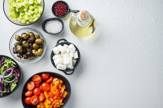 Приготовление ингредиента греческого салата на белом фоне, плоский вид сверху с копией пространства для текста