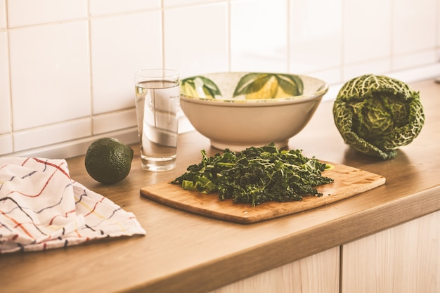 Cooking green salad from kale and avocado in the kitchen