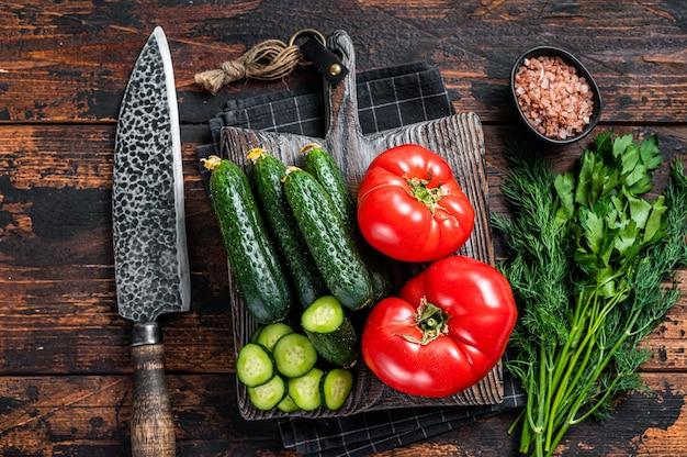 토마토, 오이, 파슬리, 허브로 녹색 야채 샐러드를 요리하세요. 어두운 나무 배경입니다. 평면도.