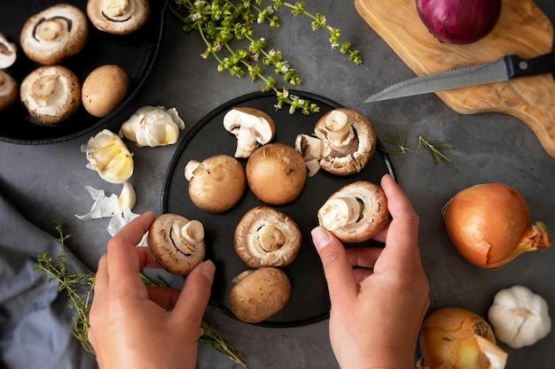 健康食品の調理。シャンピニオンキノコを持っている手、上面図。