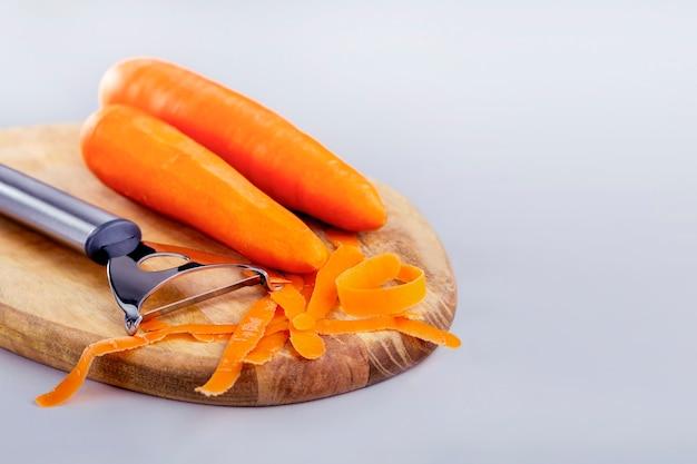 건강한 날 음식 요리. 특별한 칼로 당근 껍질을 벗기십시오. 복사 공간와 회색 배경에 나무 보드에 원시 당근.