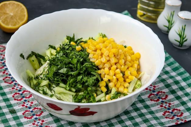 キャベツ、キュウリ、トウモロコシ、水平の写真、パセリをサラダにスライスしてヘルシーなサラダを調理する