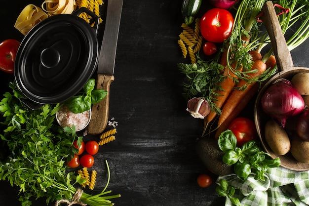 様々な野菜、キッチンテーブル、キッチンの背景に調理鍋で健康的な野菜のデトックスの概念を調理する。コピースペースを持つトップビュー。