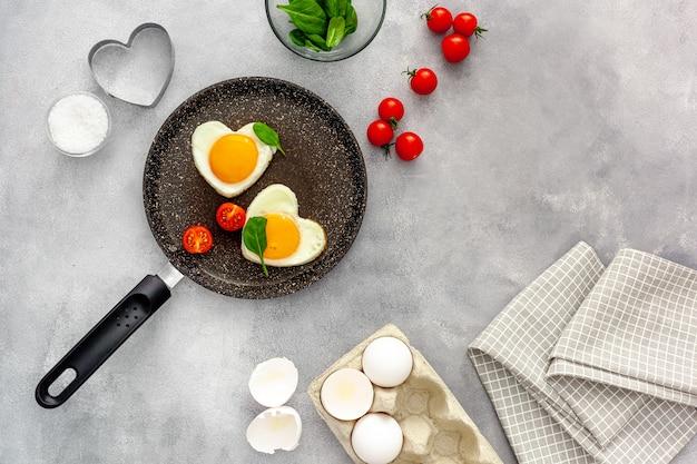 Готовим яичницу в форме сердца на сковороде с помидорами и зеленью