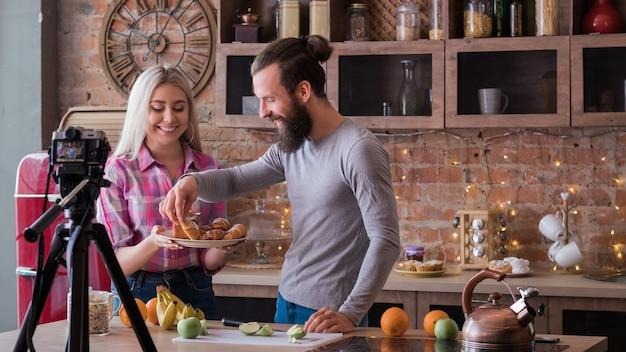요리 취미와 생활 방식. 가족 동영상 블로그. 부엌에서 젊은 부부의 비디오 스트림입니다. 과일과 패스트리가 취급합니다.