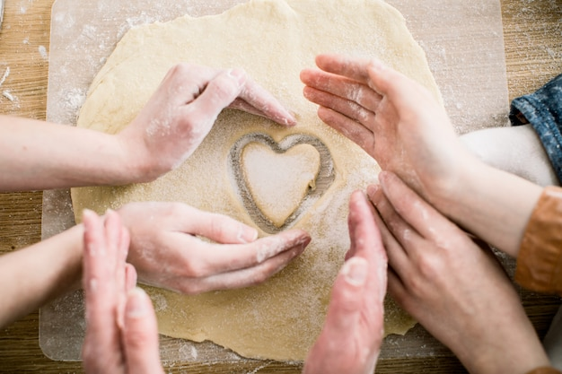 Cooking and home concept - close up of female hands making cookies from fresh dough at home. hands of three women hold cookie in form of heart