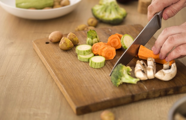 Cooking at home concept man hands slices vegetables for cooking vegetarian healthy food