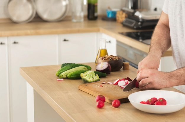 Cooking at home concept man slices fresh vegetables for cooking vegetarian healthy food