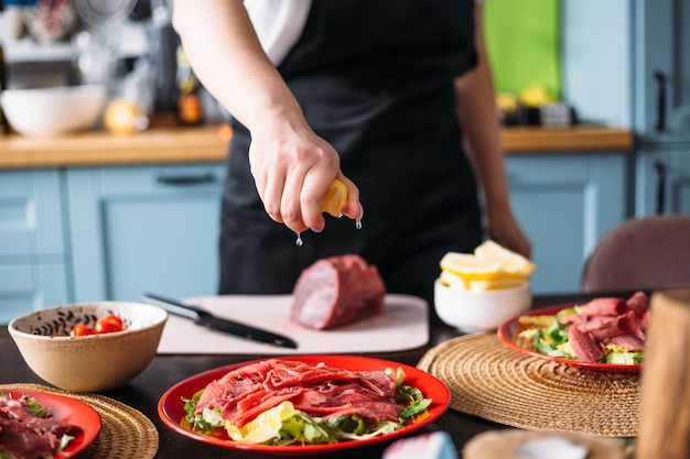 Cooking at home in kitchen italian carpaccio made from beef