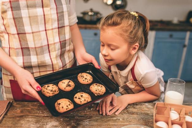自家製ケーキを調理しています。幸せな愛情のある家族が一緒にパン屋を準備しています。母と子の娘の女の子はクッキーを調理し、キッチンで楽しんでいます。ベビースニッフィングクッキー