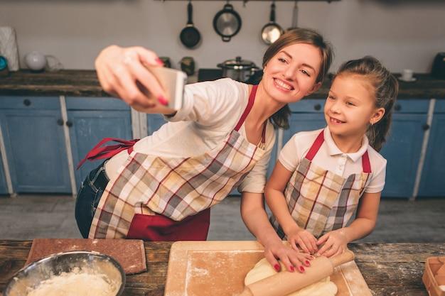 自家製ケーキを調理しています。幸せな愛情のある家族が一緒にパン屋を準備しています。母と子の娘の女の子はクッキーを調理し、キッチンで楽しんでいます。生地を転がします。自撮りを作る