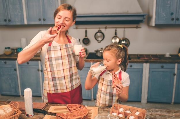 수제 케이크 요리. 행복한 사랑의 가족이 함께 빵집을 준비하고 있습니다. 어머니와 자식 딸 부엌에서 재미. 신선한 수제 케이크를 먹는다