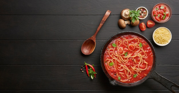Cooking homemade italian pasta spaghetti with tomato sauce in cast iron pan served with red chili pepper, fresh basil, cherry-tomatoes and spices over black rustic wooden table.
