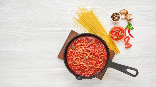 Cooking homemade noodles in boiled tomato sauce in cast iron pan served with chili pepper, fresh basil, cherry-tomatoes and spices over white texture wooden table, ingredients food concept