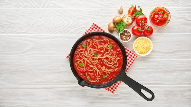 Cooking homemade pasta with tomato sauce in cast iron pan served with chili pepper, fresh basil, cherry-tomatoes and spices over white texture wooden table, ingredients food concept