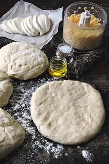 自家製ピザを調理しています。ピザ生地、小麦粉、モッツァレラチーズ、おろしチーズ。フラットレイ。