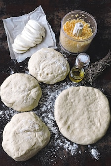 自家製ピザを調理しています。ピザ生地、小麦粉、モッツァレラチーズ、おろしチーズ。フラットレイ。 Premium写真