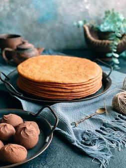 집에서 꿀 케이크 요리하기. 접시에 쌓인 둥근 구운 케이크 층.