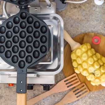 Cooking hong kong waffles with chocolate filling on a special waffle iron