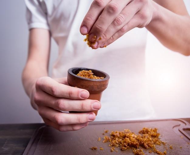 バーで水ギセルを調理します。たばこをボウルに切る。レストラン、水ギセルバー、喫煙カフェ。