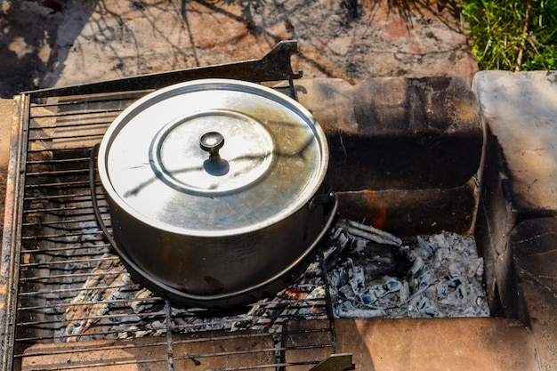 Готовим в походе в котле над огнем, из котла идет белый дым