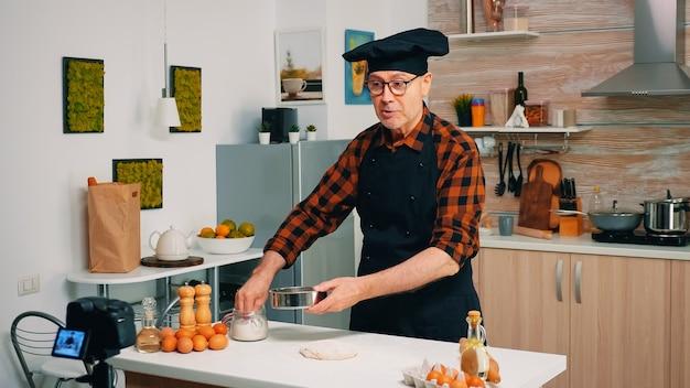 Готовим перед профессиональной камерой во время съемок нового рецепта. блогер на пенсии, повар, влиятельный человек, используя интернет-технологии, общается, ведет блог в социальных сетях с помощью цифрового оборудования.