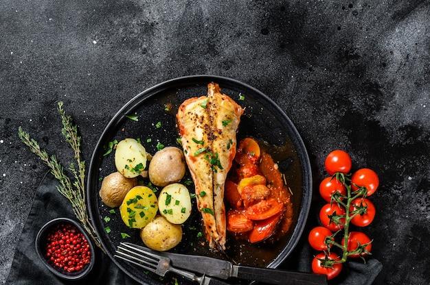 ベイクドポテト添えトマトアンコウフィッシュで調理。新鮮なシーフード。黒の背景