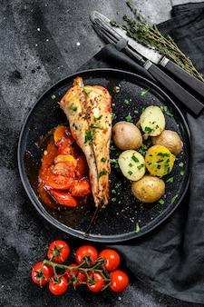 구운 감자와 토마토 monkfish 물고기 요리. 신선한 해산물. 검은 표면. 평면도