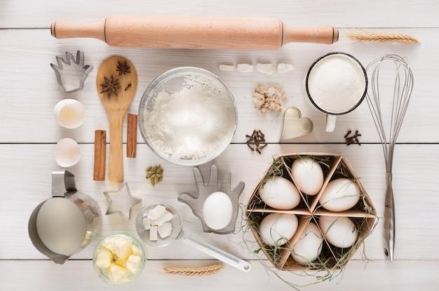 イースト生地とペストリーの白い素朴な木材の食材と調理器具。トップビュー、フラットレイアウト