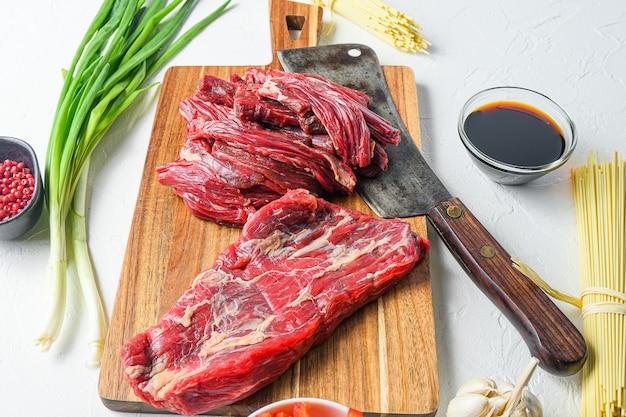 ビーフステーキを使った自家製炒め麺を作るための食材。白いコンクリートのテーブルの側面図。
