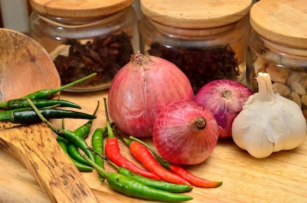 料理の材料。木の板に玉ねぎとニンニクのスパイスとハーブ