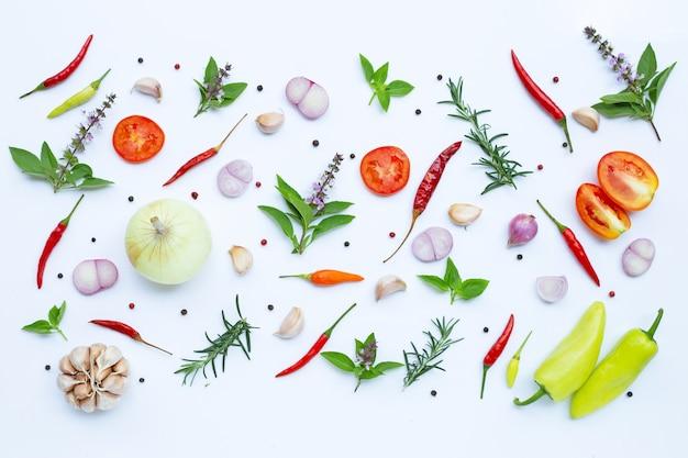 食材、白い壁に様々な新鮮な野菜やハーブ。健康的な食事の概念