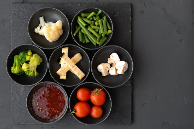 Приготовление ингредиентов овощей в небольших мисках на черном фоне