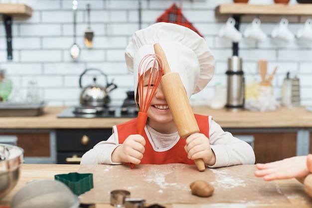 Готовить это весело. маленькая девочка шеф-повар, играя с мукой. молодая девушка работает на тесто со скалкой, чтобы сделать пряники печенье.