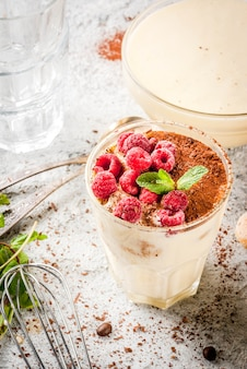 Cooking italian food dessert tiramisu, with all the necessary ingredients cocoa, coffee, mascarpone cheese, mint and raspberries