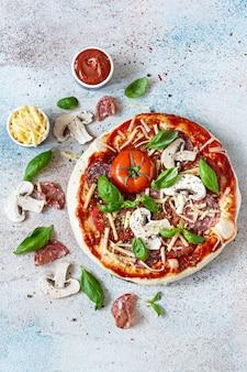 イタリアのピザをトマトソースで調理するフレッシュトマトチーズマッシュルームサラミスライスとバジル