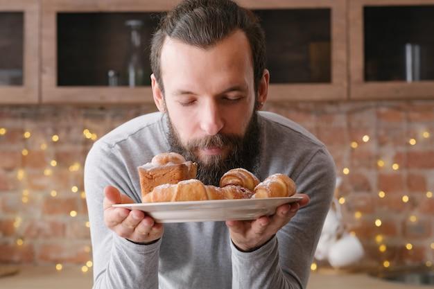 요리하는 사람. 제빵 사업. 신선한 케이크와 패스트리 접시와 함께 기쁘게 젊은 요리사