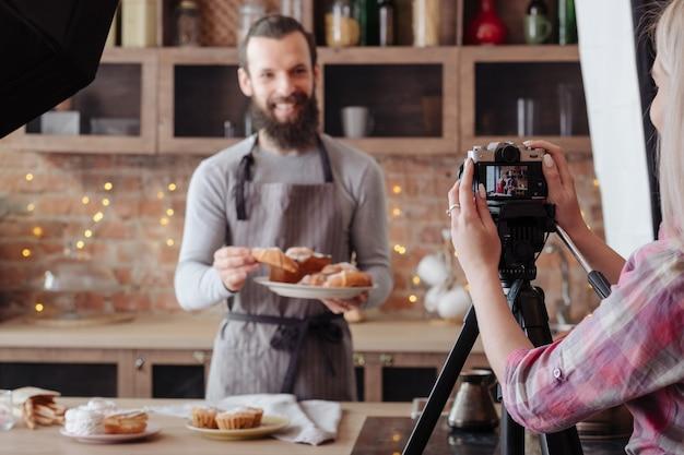 요리하는 사람. 빵 굽기. 신선한 케이크와 패스트리 접시와 앞치마에 흥분된 요리사. 백 스테이지 사진.