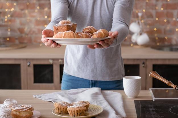 요리하는 사람. 취미와 생활 방식. 맛있는 신선한 케이크와 패스트리가 손에 든 접시