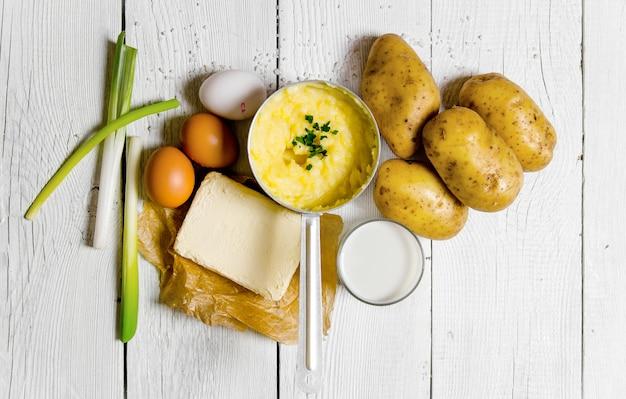 マッシュポテトの材料:ジャガイモ、ミルク、卵、バターなどを白い木製のテーブルで調理する