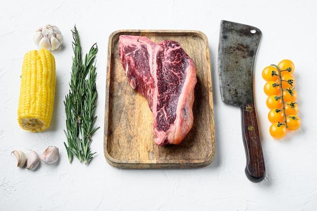 고기 배경 요리. 흰색에 그릴용 향신료와 허브를 곁들인 원시 숙성 쇠고기 티본 스테이크