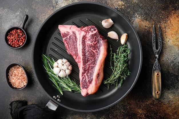 Приготовление мяса фон. сырой выдержанный стейк из говядины на косточке, со специями и травами для гриля, на чугунной сковороде, на старом темном деревенском фоне, плоский вид сверху