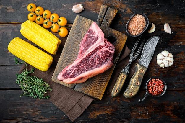 Приготовление мяса фон. сырой выдержанный стейк из говядины на косточке, со специями и травами для гриля, на фоне старого темного деревянного стола, плоская планировка, вид сверху