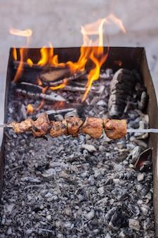 火で肉を調理します。グリルでシシカバブ。冬はグリルが屋外で点灯します。グリルでシシカバブを炒める