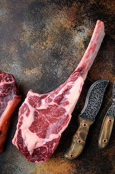 Cooking meat. raw tomahawk steak, with spices and herbs for cooking set, on old dark rustic