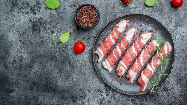 Приготовление мясных рулетов в беконе с зеленью и специями. кетогенная диета, вид сверху. место для текста.