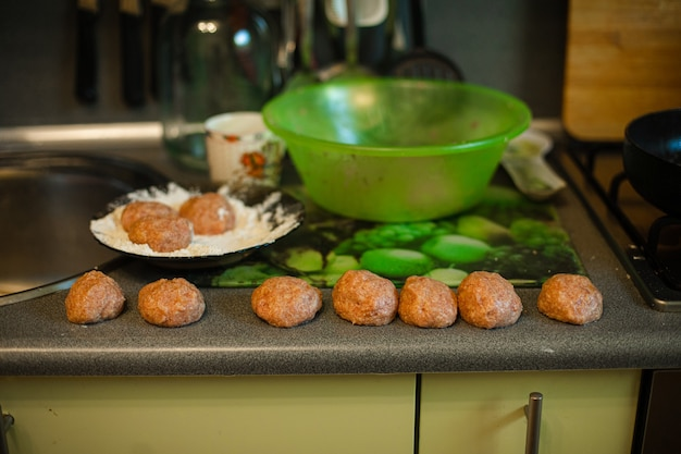 Cooking meatballs, ready mince lies by roasting on the kitchen table