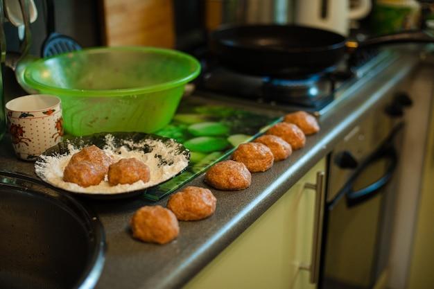 ミートボールを調理し、台所のテーブルでローストすることでミンチの準備ができています