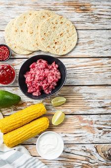 Приготовление мексиканских ингредиентов тако с рубленым органическим мясом, кукурузой, кальсой над белым текстурированным деревянным столом, вид сверху с пространством для текста.