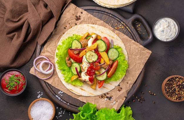 茶色の壁でメキシコのタコスを調理しています。トルティーヤ、肉、フライドポテト、野菜、そしてホットソース。